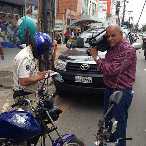 Agente de trânsito no momento exato em que aplicava a multa; cinegrafista Cachorrão