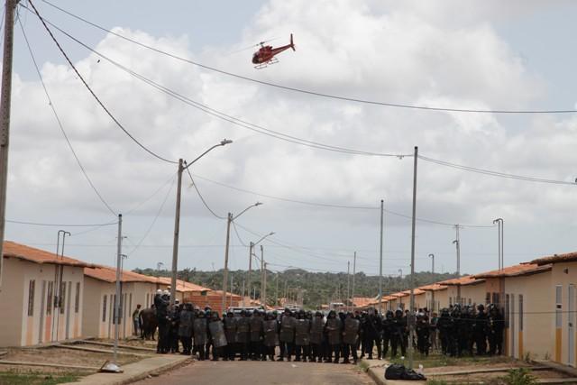 Policias posicionados durante a desocupação do Nova Terra; helicóptero sobrevoa conjunto