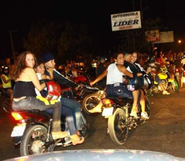 Três pessoas sem capacete em cada moto