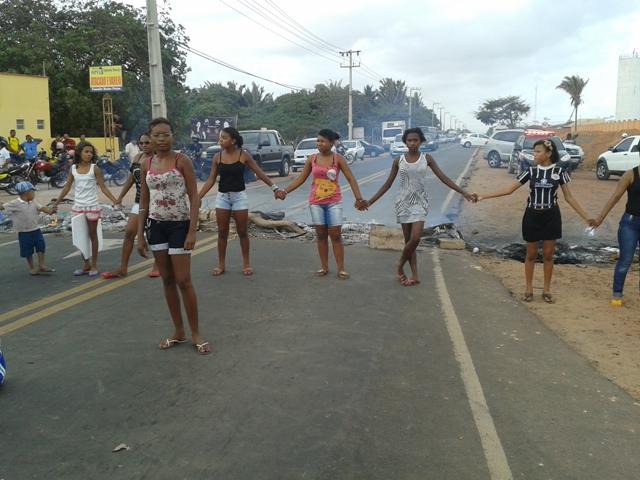 Crianças e adolescentes de mãos dadas, no meio da pista, foram usadas para bloquear a estrada