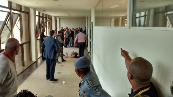 Erinaldo Almeida Soeiro caído no corredor do fórum após balear investigador e ser alvejado por outro policial