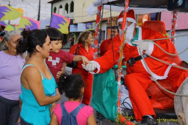 Papai Noel entrega doces a crianças durante sua passagem pelo conjunto Maiobão