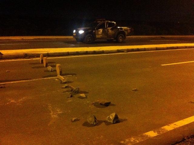 Pedras atravessadas por criminosos para interceptar motoristas na Avenida Quarto Centenário e ao fundo viatura do Batalhão de Choque que flagrou e desmontou barricada