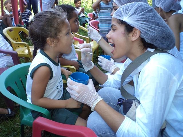 Menina é examinada por odontóloga em ação de saúde promovida pela Faculdade Florence