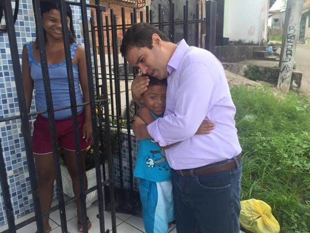 Edivaldo Holanda Júnior abraça garoto sob o olhar de contentamento da mãe, em evento público recente, na Vila Palmeira