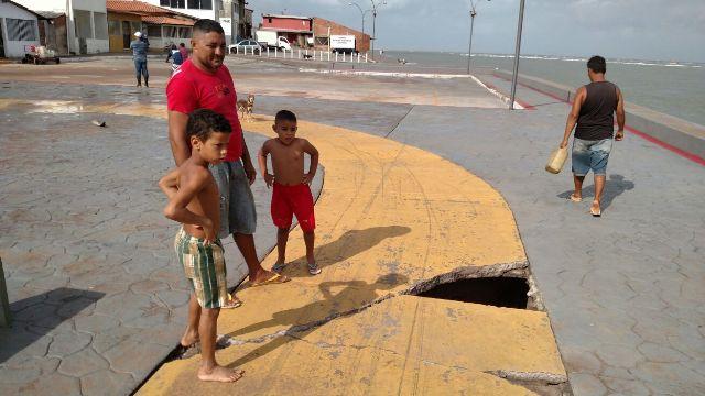 Homem e crianças observam buraco causado pela maré em trecho do calçadão da praia da Raposa