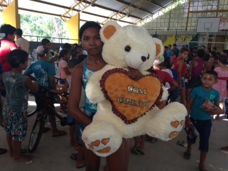 Menina exibe urso de pelúcia que ganhou de presente durante a festa