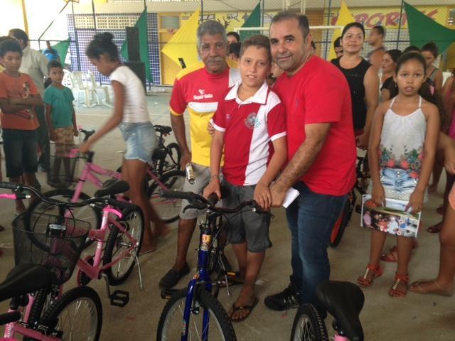 Prefeito Sydnei Pereira entrega bicicleta a menino durante a confraternização