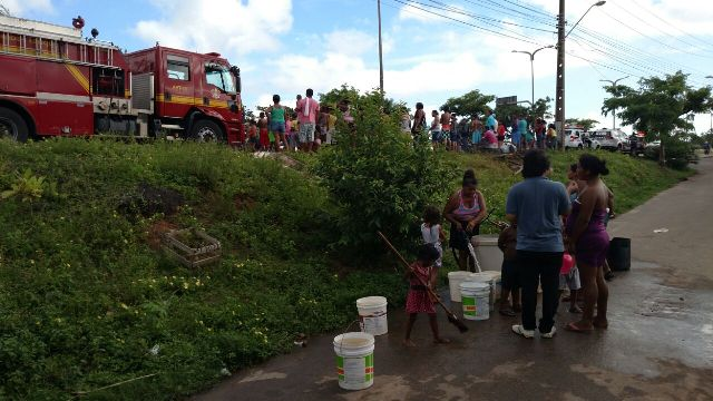 Populares enchem baldes com água do carro do Corpo de Bombeiros acionado para apagar fogo na pista