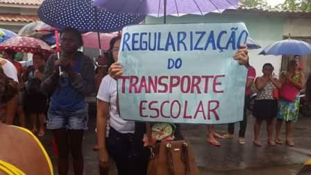 Funcionária exibe cartaz cobrando regularização do transporte escolar