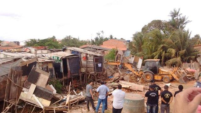 Escavadeira avança sobre palafitas durante a operação de desocupação da margem da avenida