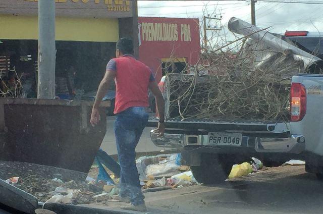 Galhos podres de árvore são jogados em via pública por homens que usavam o carro oficial