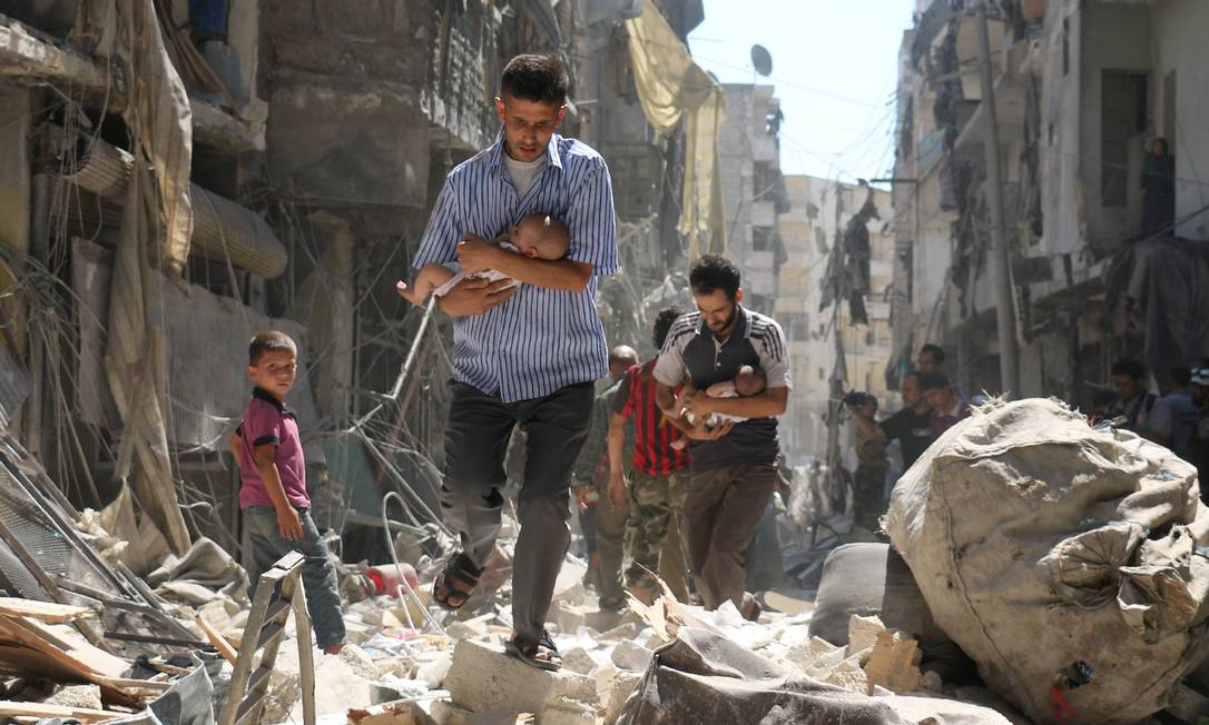 63304113_AFP-PICTURES-OF-THE-YEAR-2016Syrian-men-carrying-babies-make-their-way-through-the-rubble-o