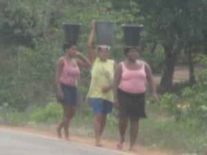 Moradoras da Vila Lobão com baldes na cabeça. (Foto/Divulgação)