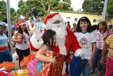 Papai Noel entregando presentes e tirando fotos com alunos da APAE em Ação Social de Natal da Cemar.