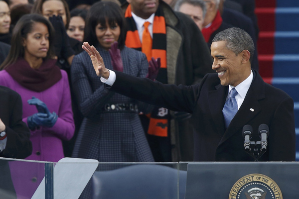 U.S. first lady Michelle Obama applauds and daughter Malia looks on as U.S. President Barack Obama speaks after he took the oath of office during swearing-in ceremonies on the West Front of the U.S. Capitol in Washington