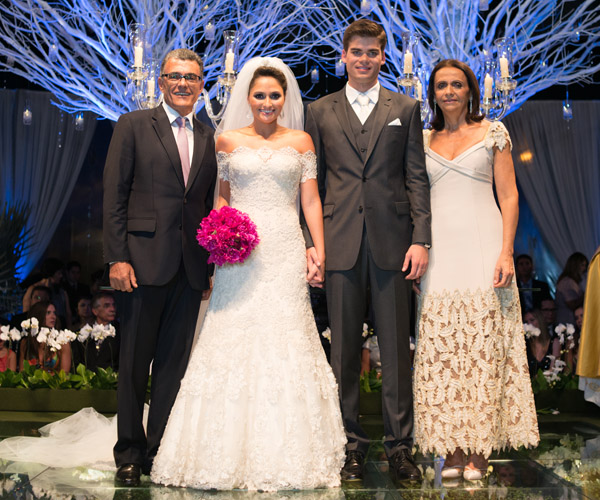 """Após o """"Si"""", os agora recém-casados posam com os pais dela. Falando nisso, foi a mãe da noiva quem conduziu toda a produção da noite, com o auxílio de bom gosto de Pergentino Holanda."""