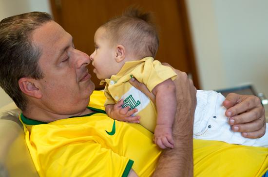 Eduardo Campos, há um mês, quando assistia a um jogo da Copa do Mundo ao lado da família. Na foto, o candidato à presidência com o filho caçula no colo, Miguel, que é portador de Síndrome de Down e cujo nome foi escolhdo homenagem ao avô Miguel Arraes, grande nome da política em Pernambuco. (Foto: PSB)