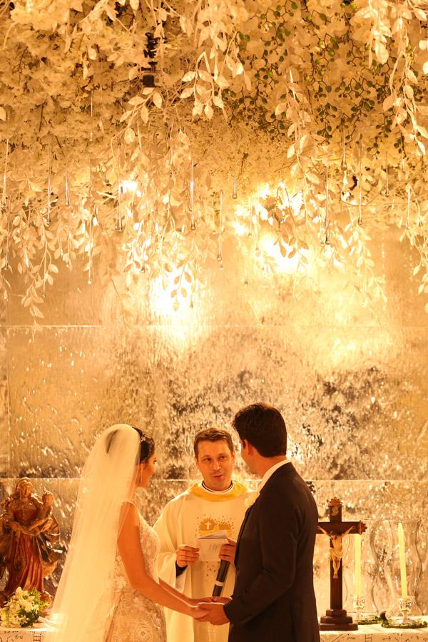 Os noivos atentos às palavras do padre Sander Patalo (Foto: Marcus Studio)